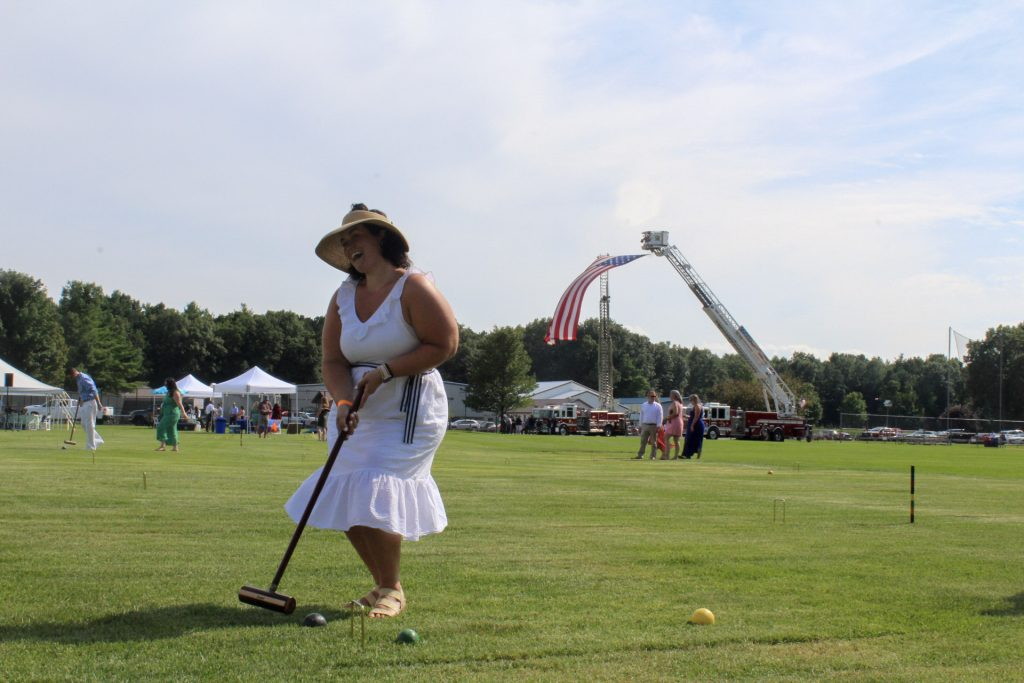 Women in white dress smiling and posing with a croquet mallet at AIM Services Croquet on the Green 2021