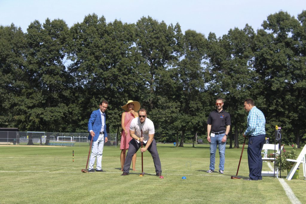 Man lining up a croquet shot while four others watch on at AIM Services Croquet on the Green 2021