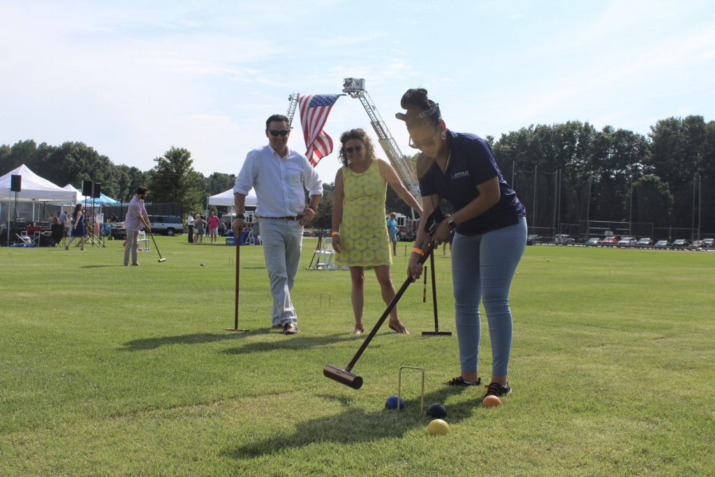 Women playing croquet while two people watch with American flag in the background at AIM Services Croquet on the Green 2021