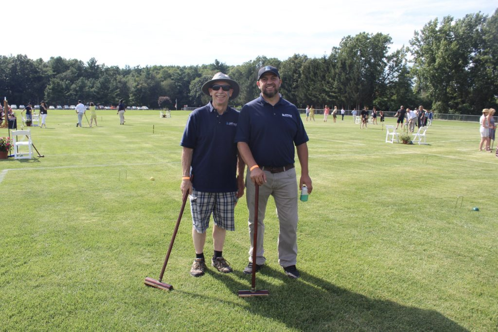 Two men in Appolo Heating polos on a croquet field at AIM Services Croquet on the Green 2021