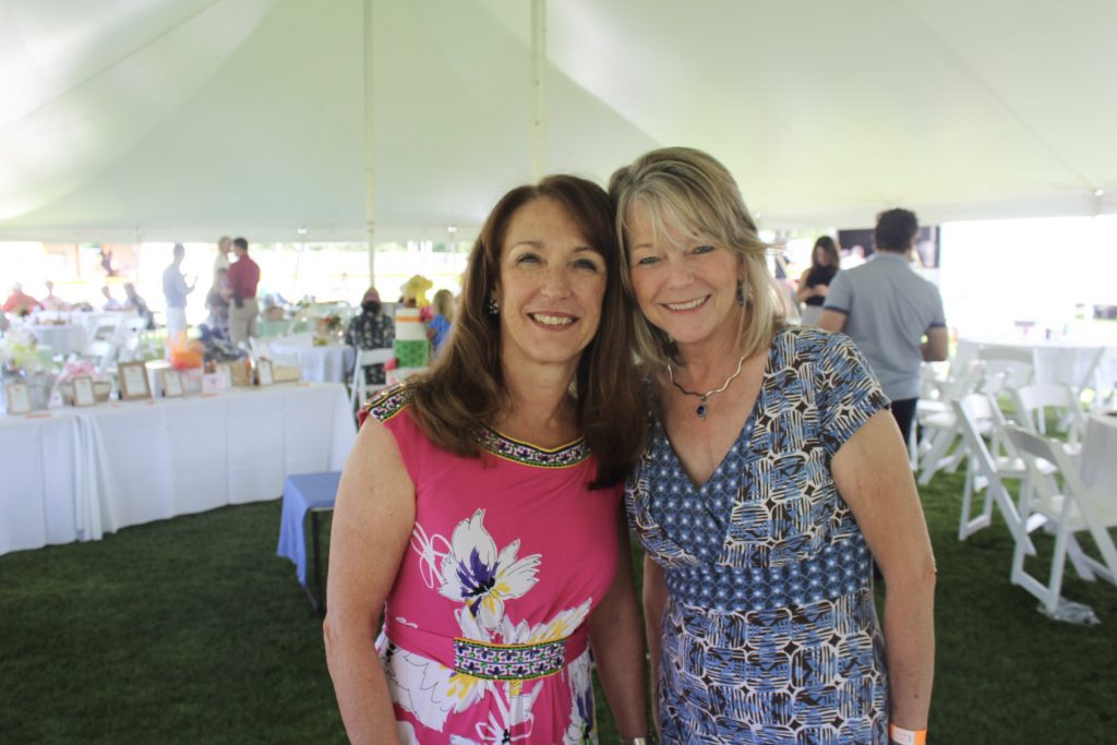 Denise Stasik and Marion Paolucci, both wearing print dresses, smiling together under the tent at AIM Services Croquet on the Green 2021
