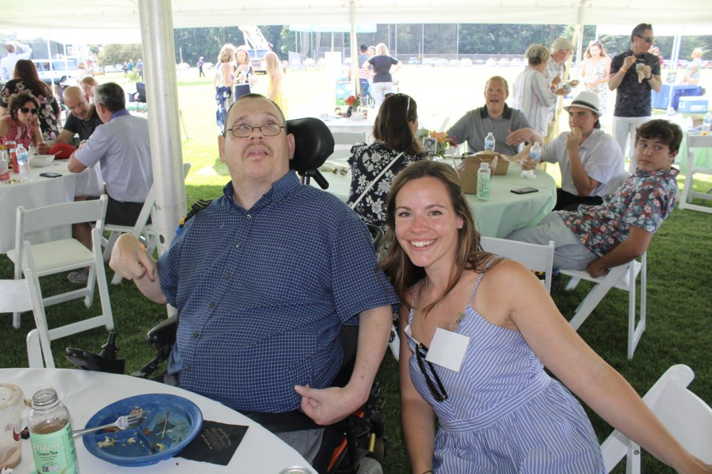 Man in blue dress shirt and wheelchair with woman in blue dress smiling next to him at AIM Services Croquet on the Green 2021
