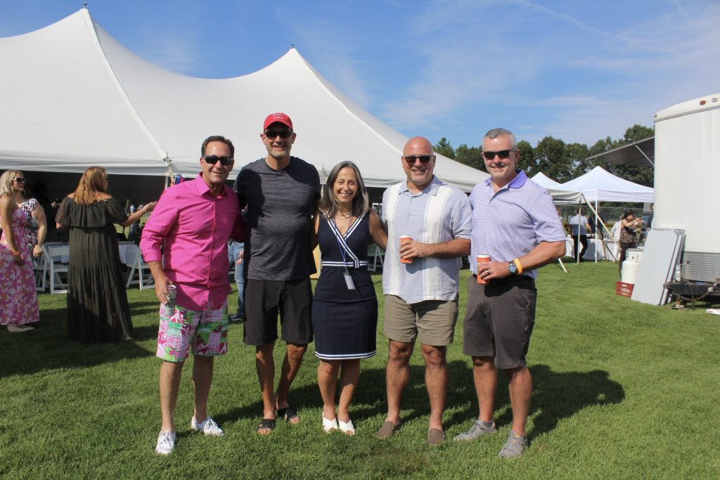 Group of five people smiling together standing in front of large tent at AIM Services Croquet on the Green 2021