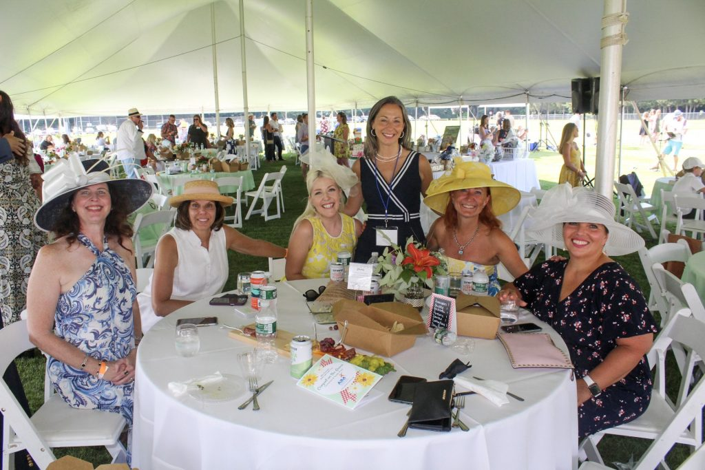 Group of five women all wearing large hats with one woman standing next to them at AIM Services Croquet on the Green 2021