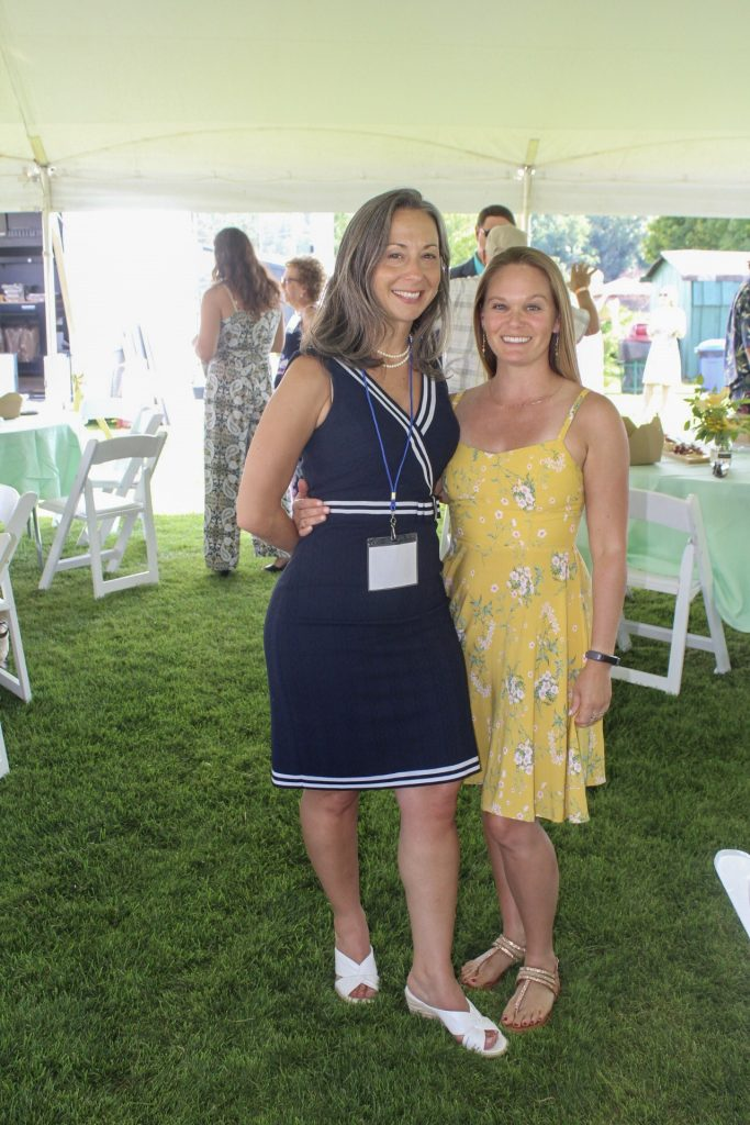Two women smiling together under the tent at AIM Services Croquet on the Green 2021
