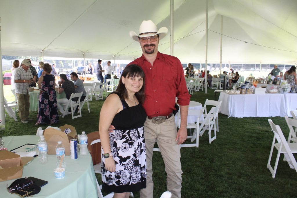 Man with cowboy hat smiling with woman in black pattern dress under the tent at AIM Services Croquet on the Green 2021