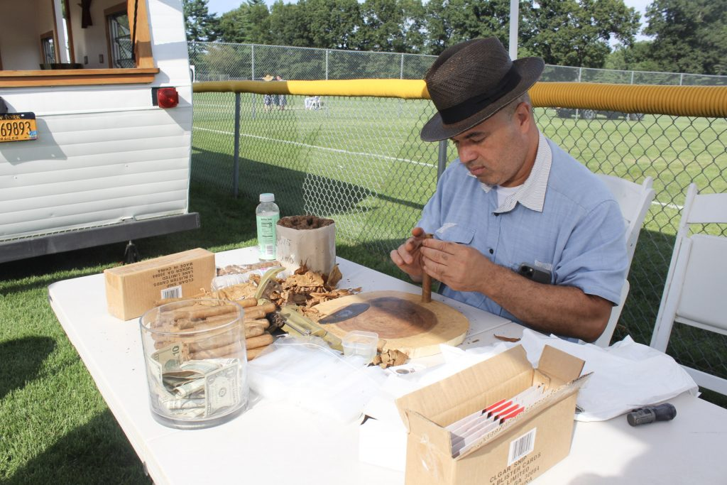 Man hand rolling cigars at AIM Services Croquet on the Green 2021