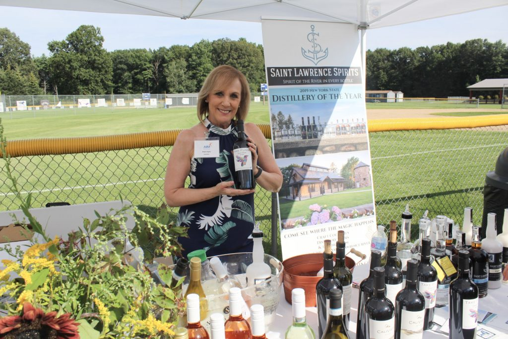 Women at a table with wine bottles holding a bottle of AIM's Take Flight wine at AIM Services Croquet on the Green 2021