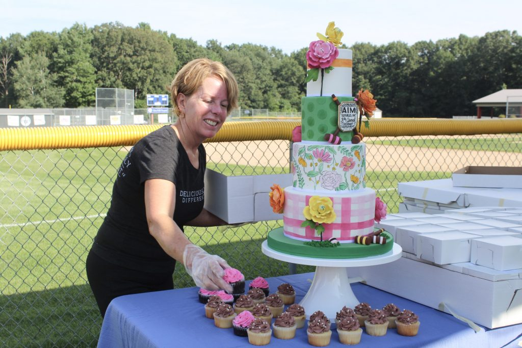 Women smiling and placing cupcakes around a large croquet themed cake at AIM Services Croquet on the Green 2021