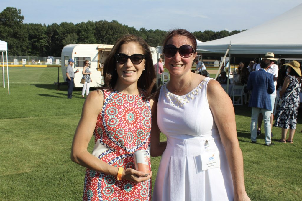 Two women, both wearing sunglasses, standing in a field at AIM Services Croquet on the Green 2021