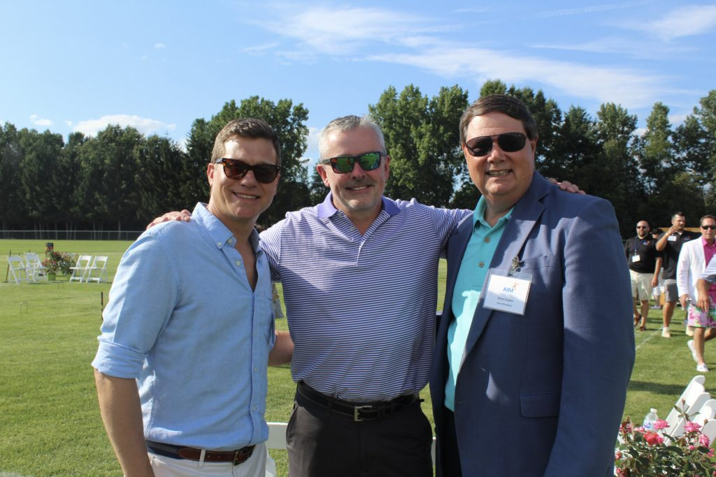 Three men, all wearing sunglasses, standing in a field at AIM Services Croquet on the Green 2021