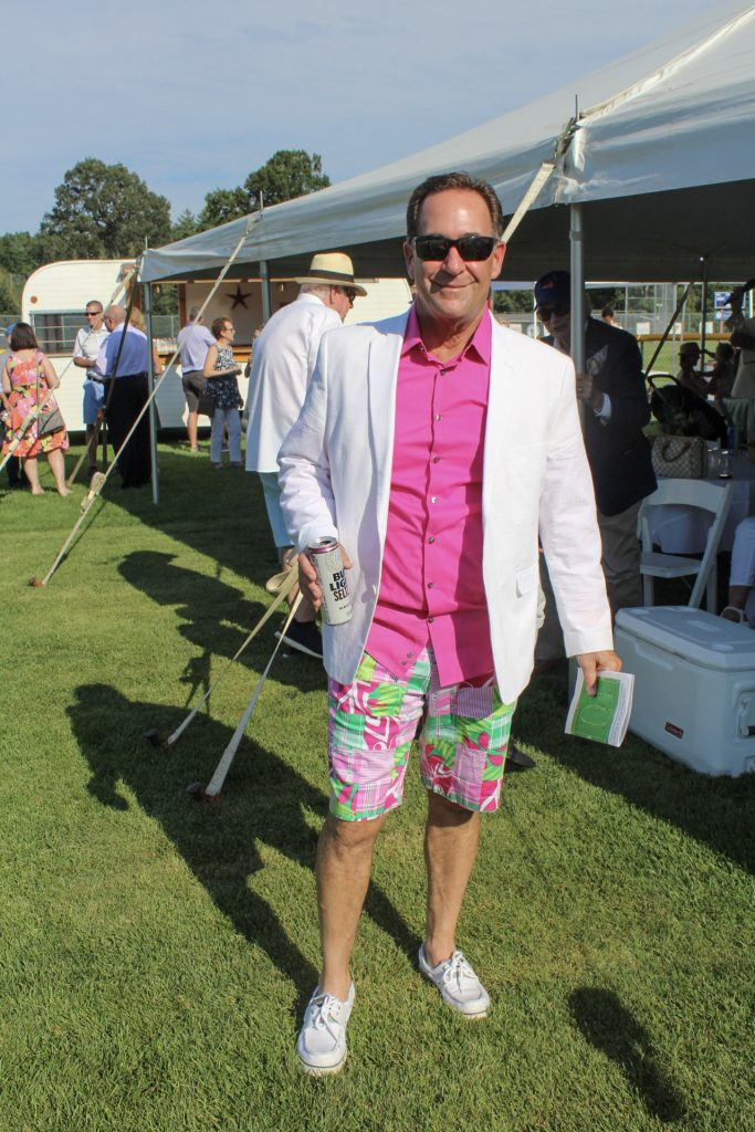 Man in bright pink shirt with pattern shorts and white blazer standing in front of the large party tent at AIM Services Croquet on the Green 2021