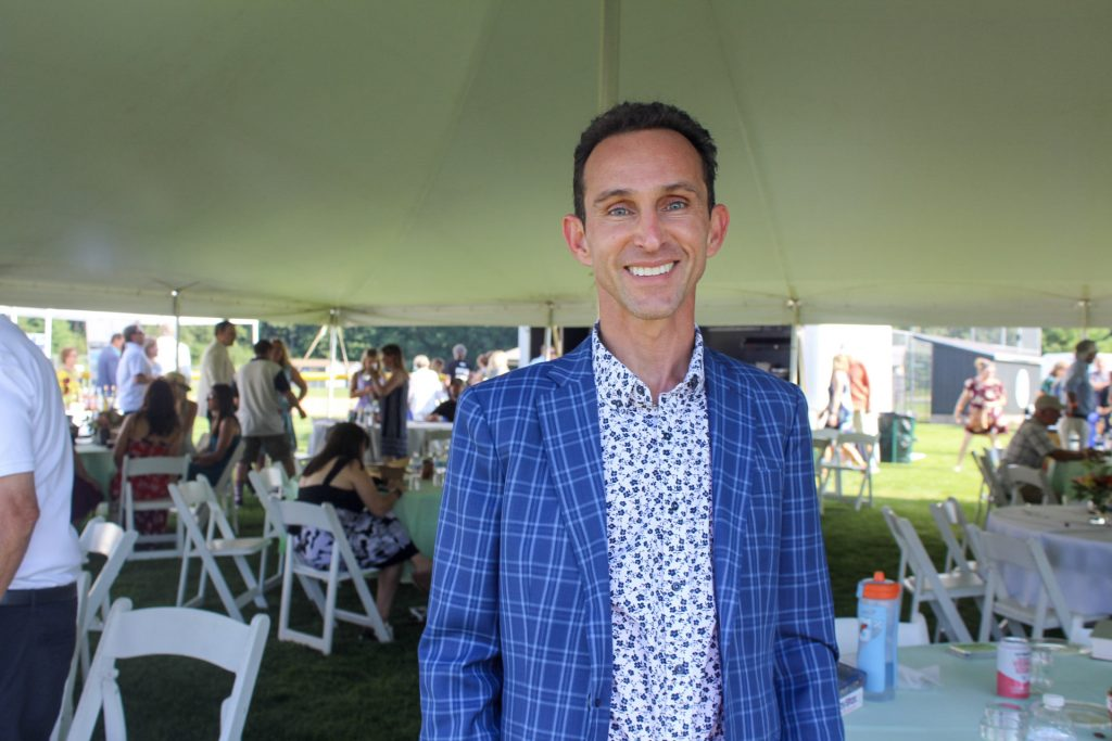 Ramon Dominguez smiling under the party tent at AIM Services Croquet on the Green 2021
