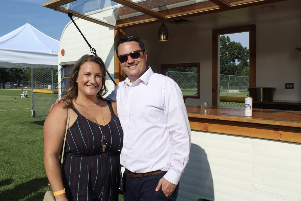 A couple standing in front of a mobile drink stand at AIM Services Croquet on the Green 2021