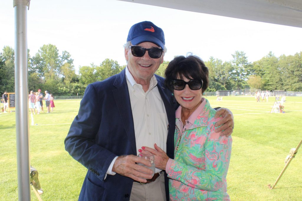 A man in a blue blazer and matching baseball cap with a woman in a zip up with flamingo design at AIM Services Croquet on the Green 2021