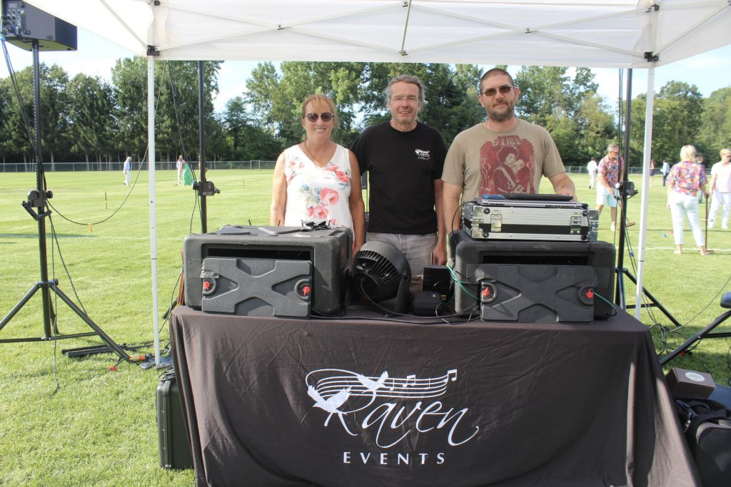 Three people standing behind Raven Events table with audio equipment on it at AIM Services Croquet on the Green 2021