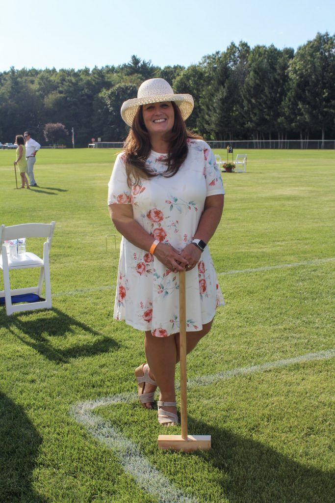 Woman in white floral dress with sun hat smiling while holding a croquet mallet at AIM Services Croquet on the Green 2021