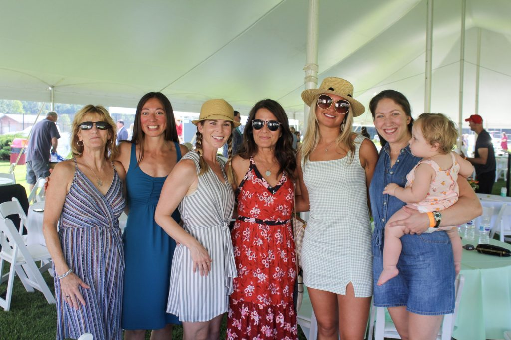 Group of six women and a baby smiling together at AIM Services Croquet on the Green 2021