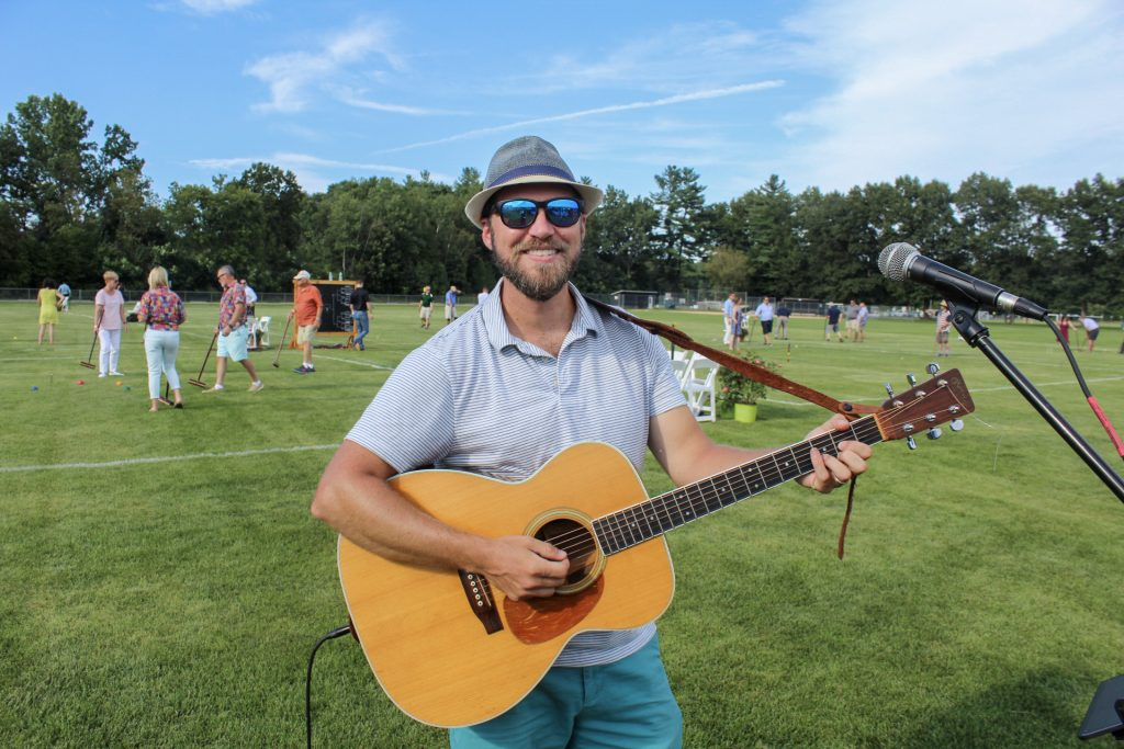 Thom Powers smiling with a guitar with the croquet fields behind him at AIM Services Croquet on the Green 2021