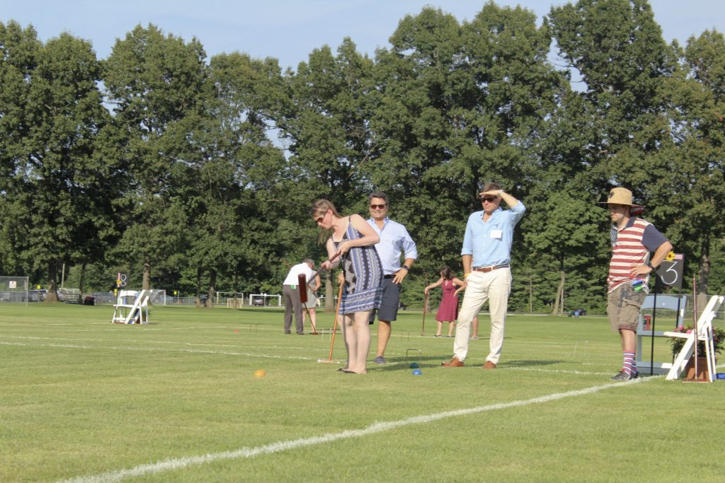Woman mid swing playing croquet with three others looking on at AIM Services Croquet on the Green 2021