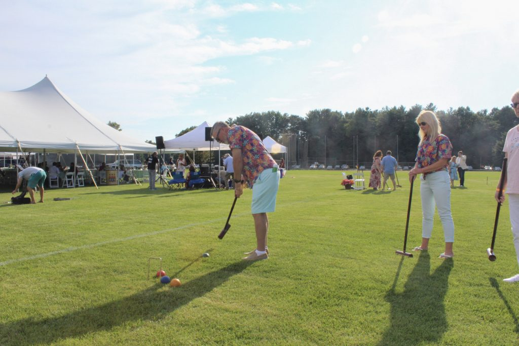Man in hawaiian shirt mid swing playing croquet while partner in matching hawaiian shirt watches at AIM Services Croquet on the Green 2021