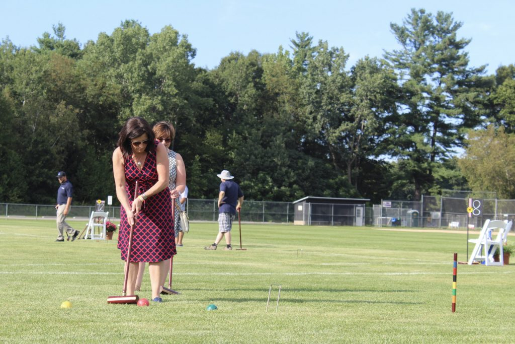 Women in navy and red patterned dress lines up a croquet shot at AIM Services Croquet on the Green 2021