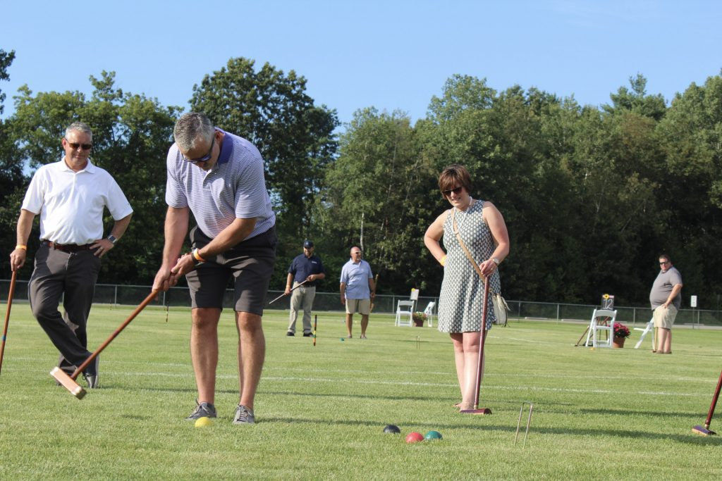 Man in striped polo swinging a mallet to hit a yellow ball while two people watch at AIM Services Croquet on the Green 2021