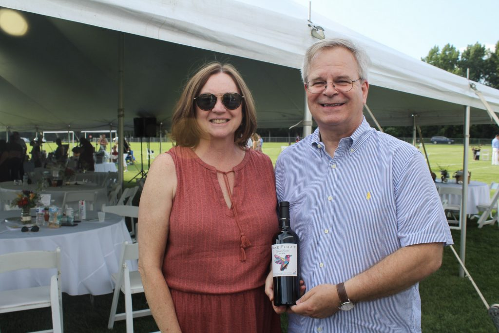 Woman in rust colored dress with man in blue and white striped button up t-shirt smiling while holding a bottle of AIM's Take Flight wine at AIM Services Croquet on the Green 2021