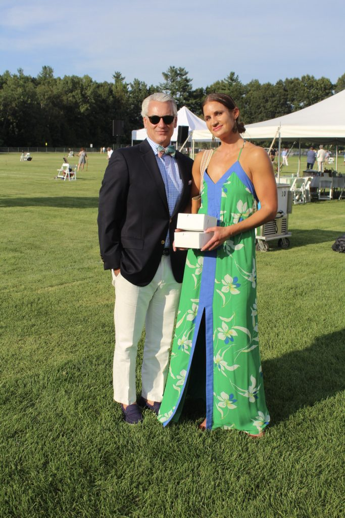 Man black blazer with woman in bright green maxi dress holding two small white boxes at AIM Services Croquet on the Green 2021