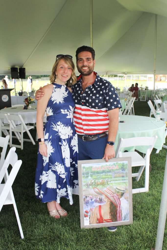 Woman in navy and white floral dress with man in American flag print button up t-shirt holding a framed print of a scene of the Saratoga Race Track at AIM Services Croquet on the Green 2021