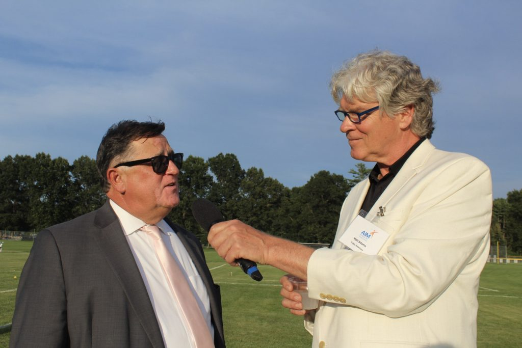 Walt Adams holding microphone up to Chris Lyons as he speaks into it with croquet field behind them at AIM Services Croquet on the Green 2021