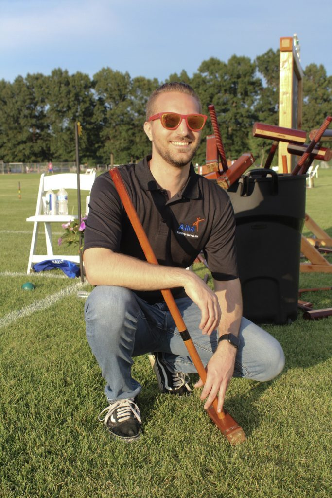 Man squatting holding a croquet mallet with a bucket of croquet mallets behind him at AIM Services Croquet on the Green 2021