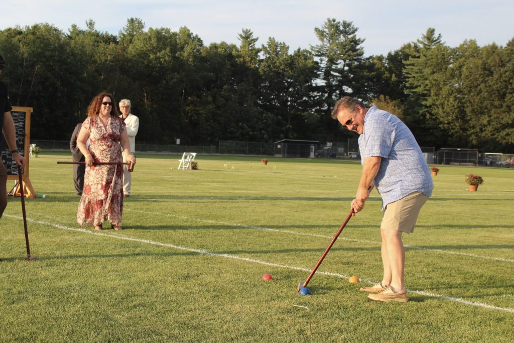 Man in blue shirt smiling why hitting croquet ball with mallet at AIM Services Croquet on the Green 2021