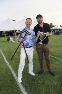 two people holding croquet mallets and a trophy