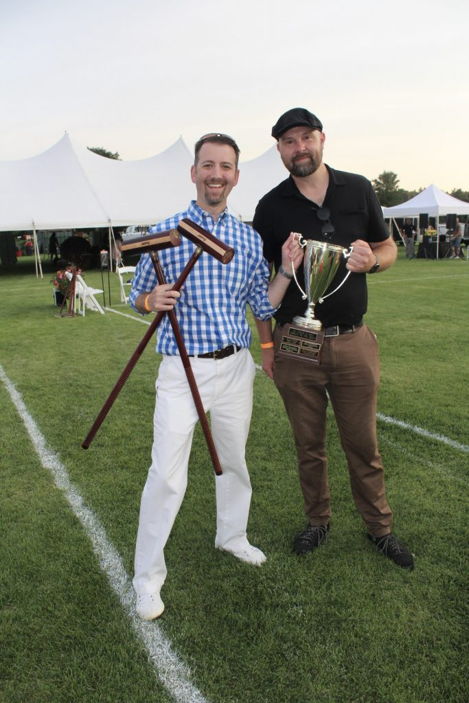 Two men holding croquet mallets and a trophy at AIM Services Croquet on the Green 2021