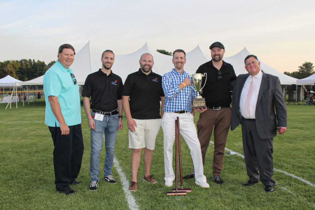 Group of six people with croquet trophy at AIM Services Croquet on the Green 2021