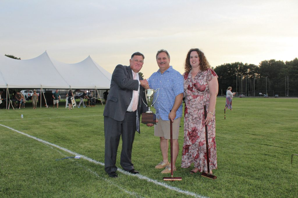Chris Lyons with Jim and Alison Norton holding a trophy at AIM Services Croquet on the Green 2021