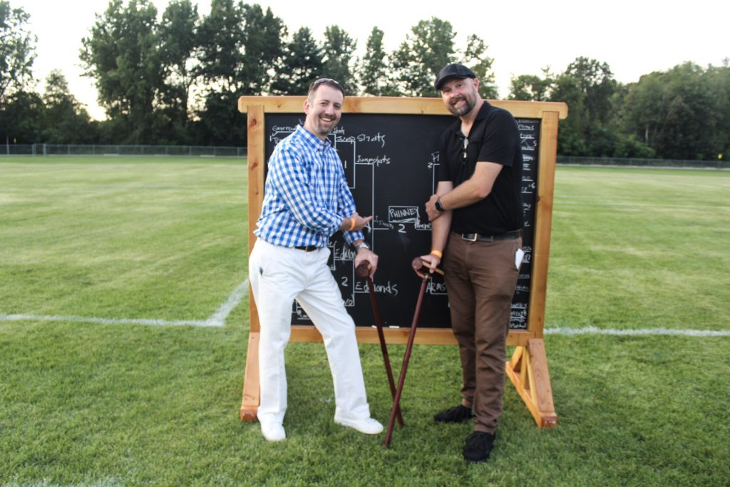 """Two men with croquet mallets pointing at the winner's name """"Phinney"""" on the scoreboard at AIM Services Croquet on the Green 2021"""