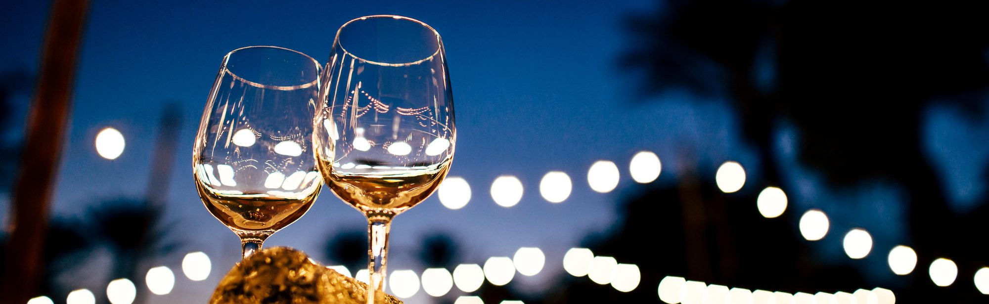 two wine glasses in front of a night sky with white lights